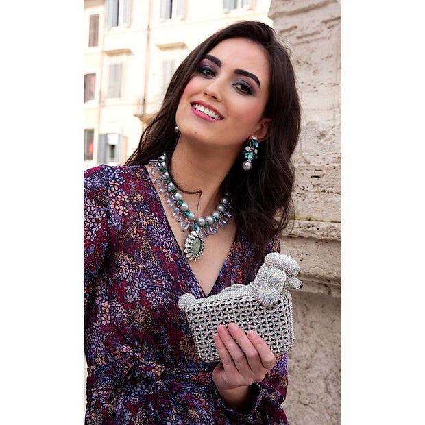 Woman Wearing Necklace Of Large Natural Agate And Large Light Grey Pearls Holding Poodle Shape Clutch- GLAM CONFIDENTIA