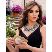 Model Wearing Emerald cut Aquamarine Earrings Matching Necklace and Holding Gold And Silver Clutch-