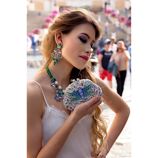 Woman Wearing Amethyst, Emerald Green Earrings And Holding Blue And Silver Dragonfly Shape Clutch