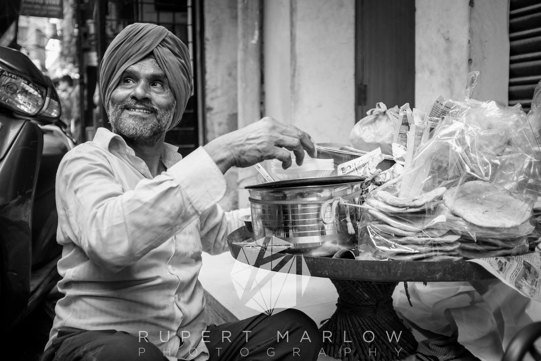 Monochrome, black and white street vendor selling breakfast and smiling broadly while looking up. He's sitting o the floor near his small table that holds his cooking equipment and ingredients. Shot in India by Rupert Marlow fine art documentary photographer in 2015