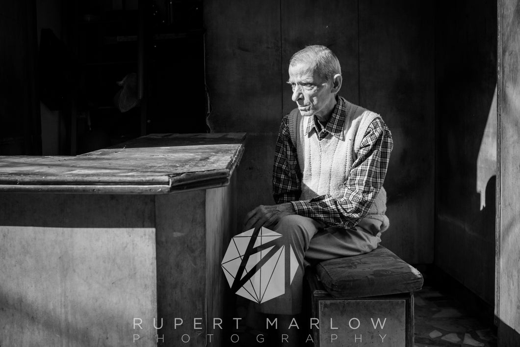 This is a monochrome, black and white photograph of a man, sitting in bright sunlight, with it shining on his face.  His left hand is accross his lap and he looks slightly stern.  The background is dark and contrasts against the bright light but you can see some shelving in the background. Shot in India by Rupert Marlow fine art documentary photographer in 2015