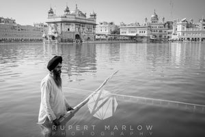 Monochrome, black and white photograph of a man, cleaning the water surface at the Golden Temple in Amritsar with a long bamboo pole, skimming the top of the water where people bathe. Shot in India by Rupert Marlow fine art documentary photographer in 2015