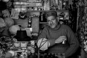 A black and white image, Monochrome of a man in Bhagsu, selling hats and bracelets of all kinds.  He is wearing a traditional hat and holding a silver looking mug.  He's wearing a sweater and is surrounded by his shop display.  He looks happy. Shot in India by Rupert Marlow fine art documentary photographer in 2015