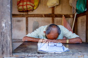 This ia a colour photograph of a man, asleep at his desk with his glasses and clipboard in the foreground.  He is in a shop and has bags hanging on the walls around him. There is a wooden post in the foreground and he has grey hair, combed over a large bald patch. Shot in India by Rupert Marlow fine art documentary photographer in 2016