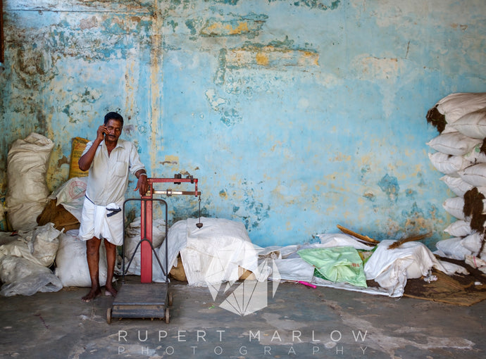 Man leaning on red weighing scales in a warehouses in Cochin. He is surrounded by sacks or bags of tea and spices. The wall behind is damp and blue. The paint is peeling off and the man is on his mobile phone, dressed in white. Shot in India by Rupert Marlow fine art documentary photographer in 2016