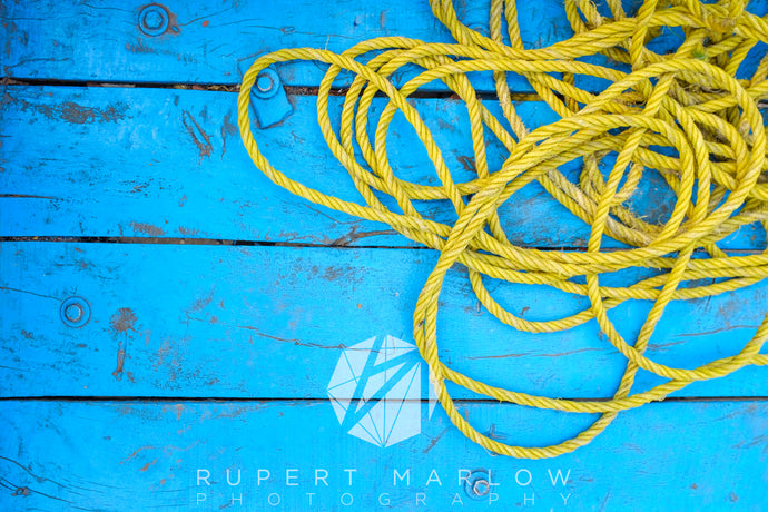 A pile of yellow rope curled up on blue wooden floorboards.  Shot in Delhi, India by Rupert Marlow fine art documentary photographer in 2015