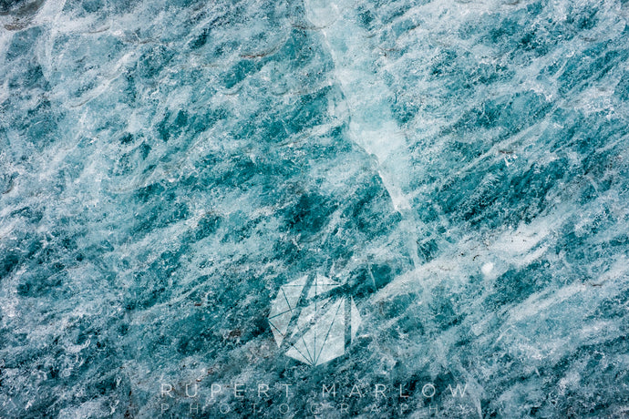 A photograph in colour into a glacier. The ice is blue as it was in the Winter and the cracks are visible. It is a green-blue colour. Shot in Iceland by Rupert Marlow fine art documentary photographer in 2015