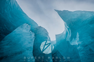 This is a view up towards the cloudy sky, from a hole in the glacier. The hole has been carved by water and left a sharp edge pointing into the image, adding drama and depth to it. The ice is a rich, blue colour, against the sky and there are varying thicknesses in the ice. Shot in Iceland by Rupert Marlow fine art documentary photographer in 2015