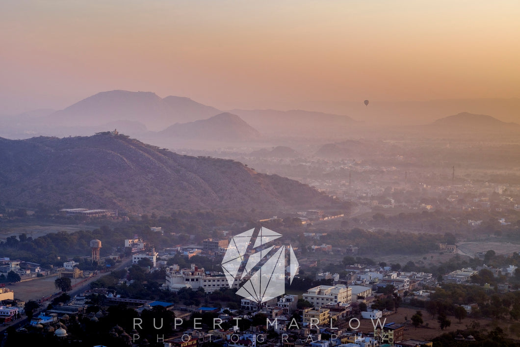 The sunrise view from Amer Fort - The Amber Fort's defensive wall showing the mist and houses below. Shot in Rajasthan, India by Rupert Marlow fine art documentary photographer in 2015