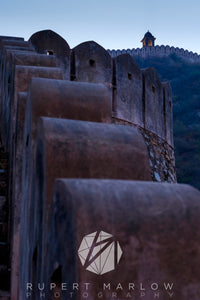 This is the defensive wall around Jaipur and on the opposite side of the valley to the Amer Fort (Amber Fort).  The wall is very thick with ramparts running up to a lookout at the top, showing as a yellow against the blue of the ain image as it was shot at dawn.