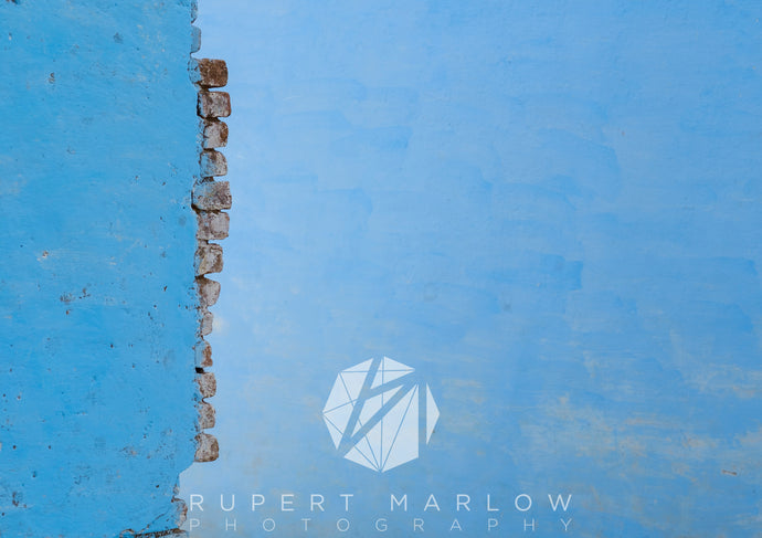 Abstract image of bricks sticking out of a wall, with a matching blue background behind them. The wall is down the left quarter of the frame and there is lots of negative space. Shot in India by Rupert Marlow fine art documentary photographer in 2015