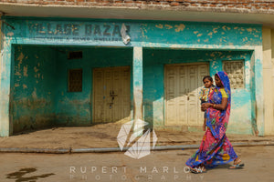 Green Village Bazar shop front with a mother carrying her child wlaking past. The sun is strong and the shadows are clear. The woman wearing a sari and is mid-stride. The paint is peeling off the walls