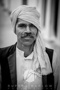 A black and white, monochrome photograph of a man with a moustache, wearing a shirt underneath a sleeveless jacket with collar. He is wearing a turbun which is hanging over his left shoulder. Shot in Khajuraho, India by Rupert Marlow fine art documentary photographer in 2015