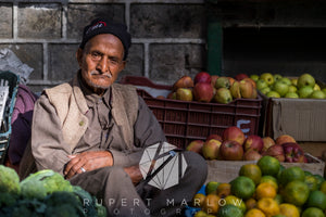 Man selling apples in McLeod Ganj in Northern india, sitting in the sun with his apples, in a waistcoat and hat. Shot in India by Rupert Marlow fine art documentary photographer in 2015