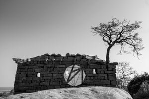 A building on top of the rocks in Mahalibalipuram, built without cement, presumably as a look-out or basic shelter and there is a tree growing out of it, among the stones. Shot in India by Rupert Marlow fine art documentary photographer in 2016