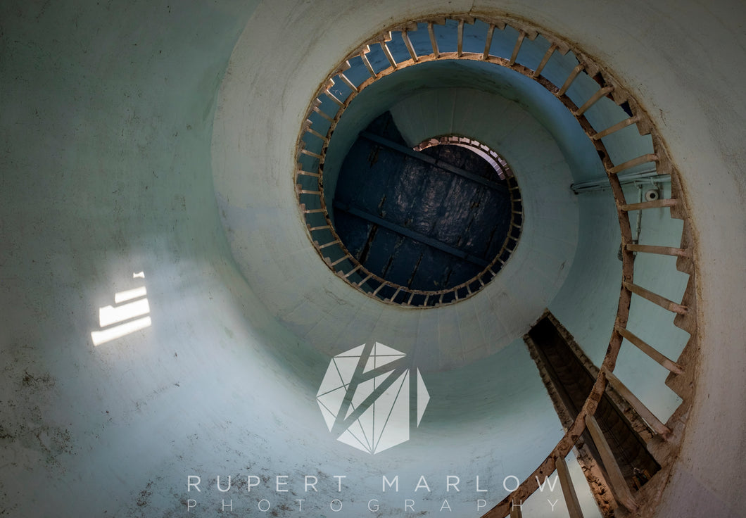 A lighthouse in Mahalibalipuram, looking up from the inside, showing the spiral staircase and a light patch on the wall as the sun shines in through the window. Shot in India by Rupert Marlow fine art documentary photographer in 2016
