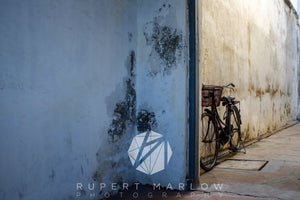 Vintage bicyle leaning against a wall in a yellow coridoor near a doorway.  The foreground it a cool blue.  There is damp in the walls and the paint is peeling in the corner. Shot in India by Rupert Marlow fine art documentary photographer in 2016