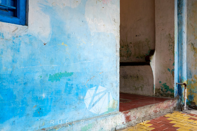A doorway in Puducherry, India with red and yellow herringbone tiles on the floor and red tiles inside up one step.  There is a bench in the hallway, built into the wall and the letters FAD written on the wall.  The wall in the foreground is blue, worn and faded and there is a darker blue window, painted in the top right corner. Shot in India by Rupert Marlow fine art documentary photographer in 2016