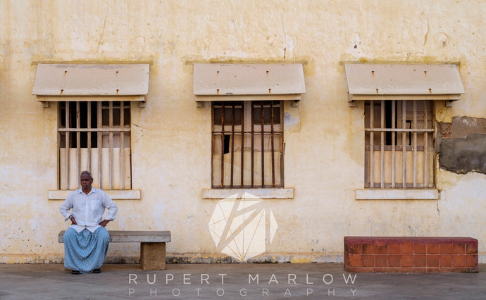 Man in blue clothes sitting on a bench in a symetrical scene, with 3 windows that have bars on the and the bench on the right is made of red brick. The walls are yellow. Shot in Pondicherry, India by Rupert Marlow, documentary fine art photographer in 2016