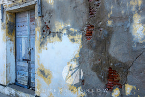 A colour photograph of a blue door set in an old wall with peeling paint and exposed bricks and render. The cement is falling out. The paint is white and yellow. The door in blue and there is some old graffiti on the wall. Shot in Pondicherry, India by Rupert Marlow fine art documentary photographer in 2015