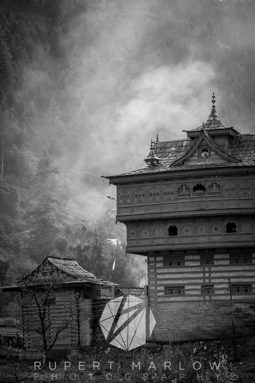 Sarahan's Royal Temple.  This was a Palace and place of worship for the people of Sarahan. It is high in the northern mountains and in this black and white image, surrounded by smoke or mist, with the trees of the mountin behind it. Shot in Sarahan, India by Rupert Marlow fine art documentary photographer in 2015