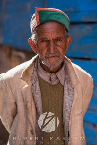 A colour photograph of a man with a grey beard, who is slightly smiling. He is wearing a grey shirt beneath a green jumper and a checked jacket under a beigh jacket. He also has a green and red hat. He is standing in front of a blue wooden building. Shot in Sarahan, India by Rupert Marlow fine art documentary photographer in 2015