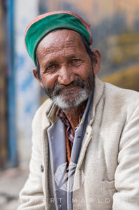 A colour photograph of a smiling man with a greying moustache and beard. He is wearing a purple shirt beneath two jackets, one is purple and the other is beige, both with collars. He has a green and red hat and is sat in front of a building. Shot in Sarahan, India by Rupert Marlow fine art documentary photographer in 2015