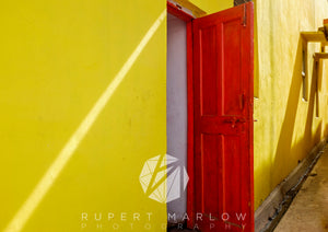 A vibrant colour photograph looking through a red door with a bolt at the top and a latch half way down. There are yellow stone walls either side of the door and a wooden skirting board. There are two windows further up from the door which are casting shadows on the wall. Shot in Udaipur, India by Rupert Marlow fine art documentary photographer in 2015