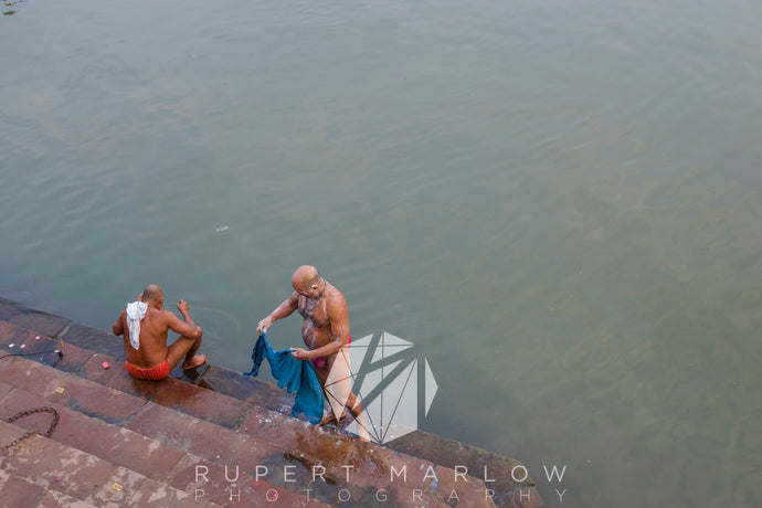 Two men, one sitting and one standing on stone steps, they are washing their laundry in the river. One man has red shorts and a white top over his shoulder, the other man has a blue shirt in his hands. They are at the bottom of approximately 5 steps on the edge of the river. Shot in Varanasi, India by Rupert Marlow fine art documentary photographer in 2015