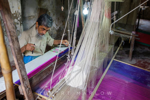 Man sitting at a loom weaving a blue and purple sari by hand. The man has a beard and the loom is made of bamboo and wood. Shot in Varanasi, India by Rupert Marlow fine art documentary photographer in 2015