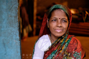 A contented lady sitting in a doorway, dressed in a sari over one shoulder. The doorway is blue and the inside is warm. She has a red spot on her forehead and looks happy.  The skin around her lips has lost some pigment probable due to vitiligo. Shot in India by Rupert Marlow fine art documentary photographer in 2015