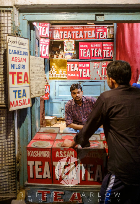 Two men at a market stall discussing tea. The shop owner is surrounded by many boxes of different types of tea. The boxes are red and he is selling Darjeeling, Assam, Nilgiri, Masala, Kashmiri, Darjeeling Green, Tulsi tea. Shot in Varanasi, India by Rupert Marlow fine art documentary photographer in 2015