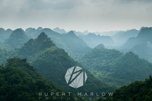 A view of the hills of Cat Ba Island, in Vietnam Halong Bay.  The steep hills fading into the distance, covered in lush green trees and vegetation. Shot in Vietnam by Rupert Marlow fine art documentary photographer in 2013