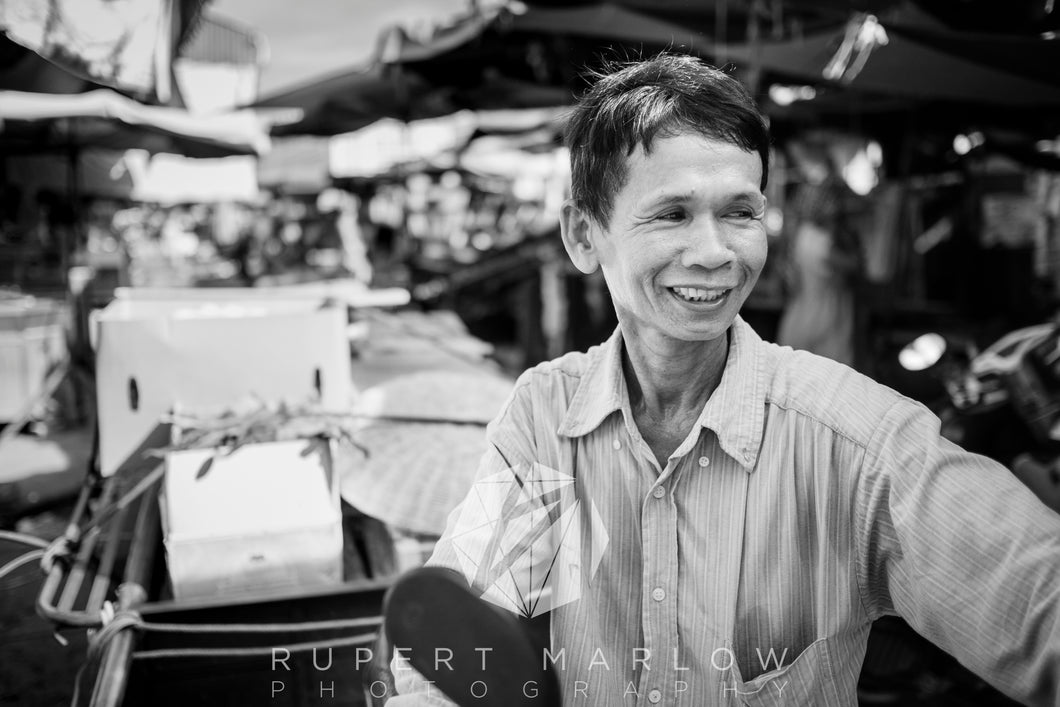 Cambodian Man on a moped, delivering to the market. He is smiling and seems very happy. The background is blurred but it is clearly a market stall, with tarpaulins protecting the food from the sun. Shot in Cambodia by Rupert Marlow fine art documentary photographer in 2018