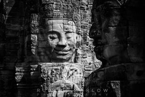 A monochrome, black and white image of The Bayon Temple in Cambodia showing 3 faces, one in light, front on and two, shaded in profile. Shot in Cambodia by Rupert Marlow fine art documentary photographer in 2018