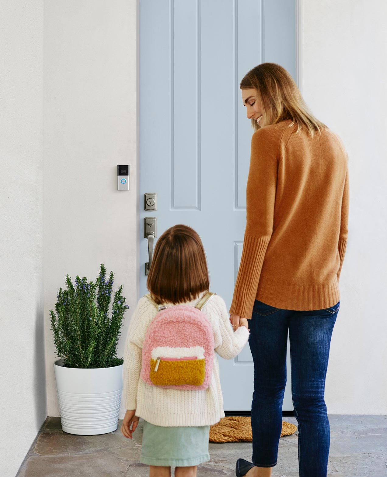 Child and Woman holding hands in the front door.