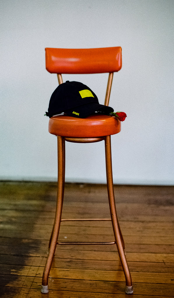 Vintage burnt orange bar stool in a room alone with black SONDR. Obscure Sorrows Dad Hat & single rose on the seat