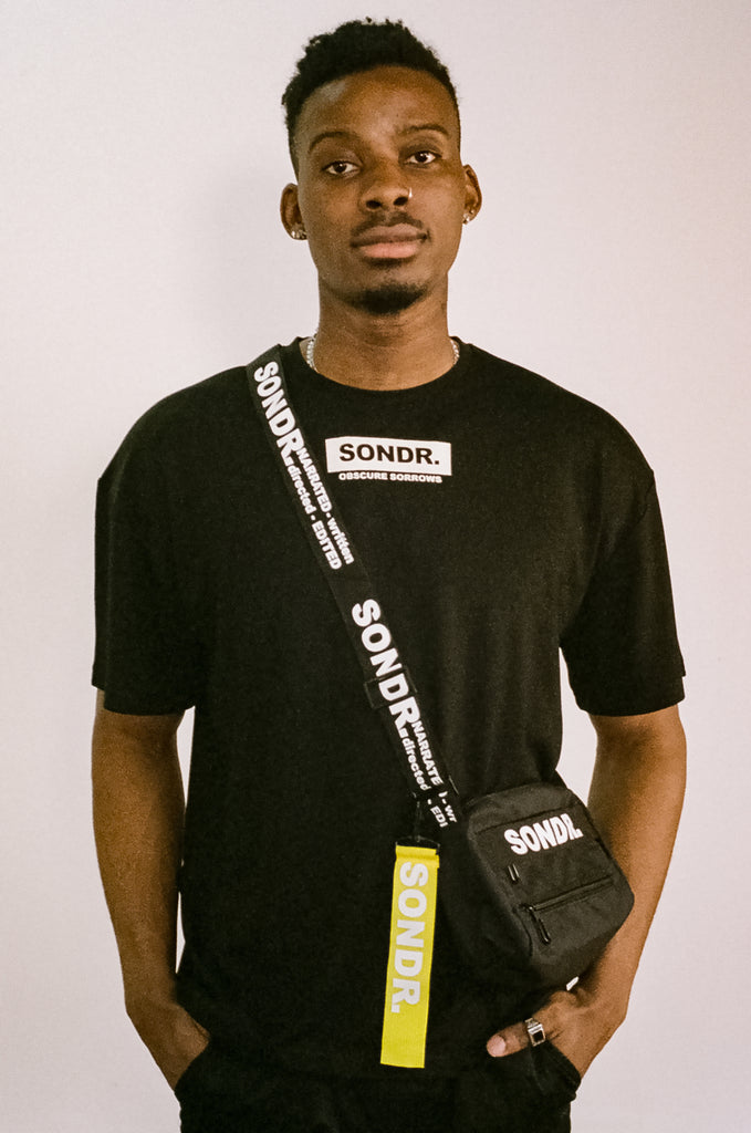 Image of Joseph Peters from Project Peters wearing a Black SONDR. Side Bag & Black SONDR. Logo T-shirt with his hands in his pockets.