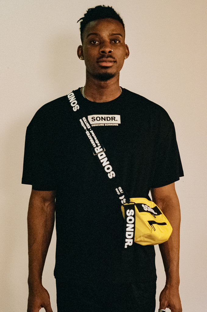 Image of Joseph Peters from Project Peters wearing a Yellow SONDR. Side Bag & Black SONDR. Logo T-shirt with his hands by his side.