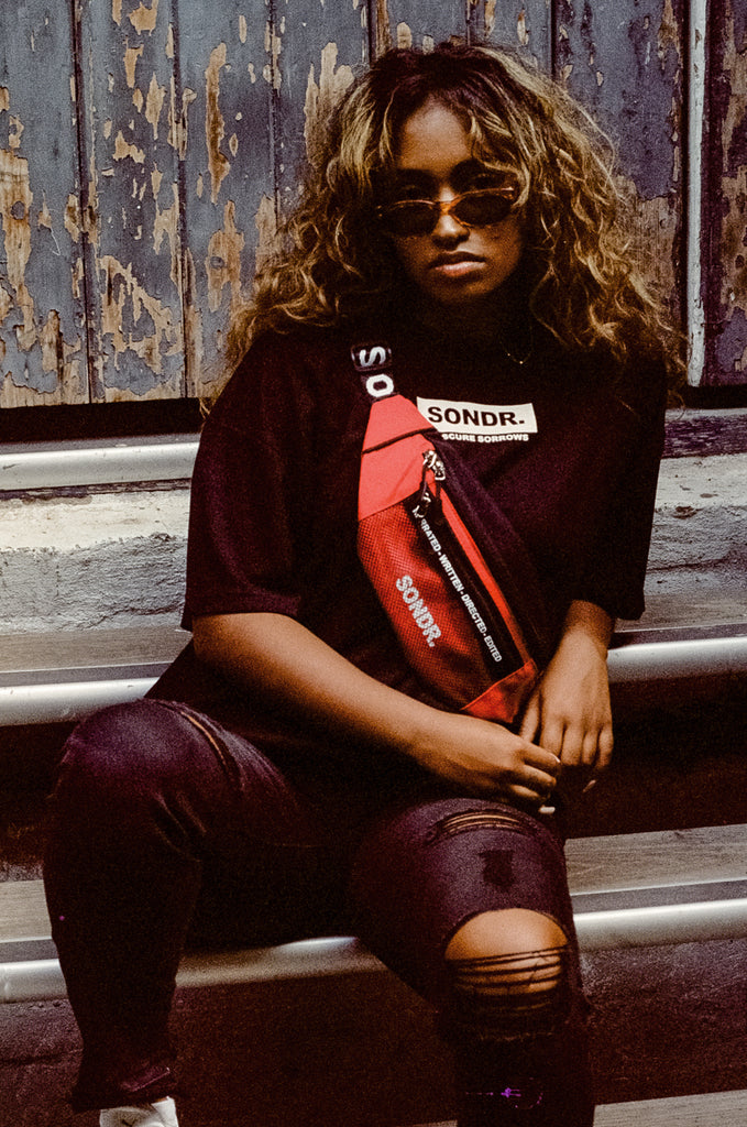 Model wearing Red Cross Body Bag sitting on stairs wearing SONDR. T-Shirt