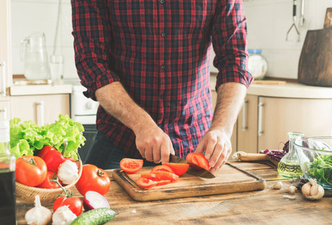 man cutting tomatoes and vegetables