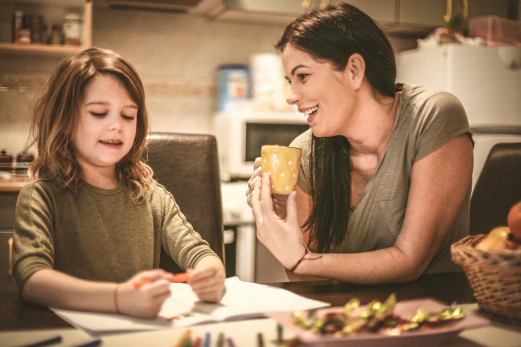relaxed mom helping daughter with homework with a cup of coffee