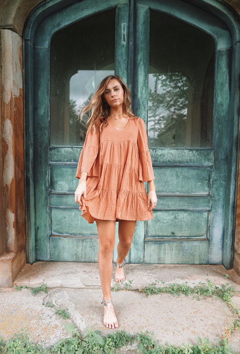 This piece features a lot of ruffles for the ultimate babydoll look. This dress is stunning on every shape and can be worn as a dress or paired with leggings as a tunic. The orange color makes it a fall essential.