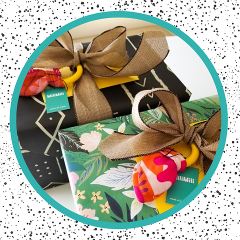 gifts wrapped in minted wrapping paper designed by independent artists, with milimili snuggle teethers tied in the ribbon