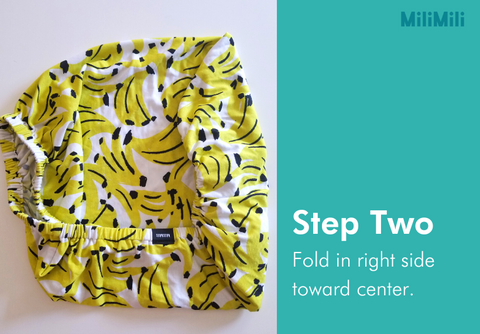 How to fold a crib sheet: step two - fold in right side towards center. Banana print cribsheet from MiliMili.