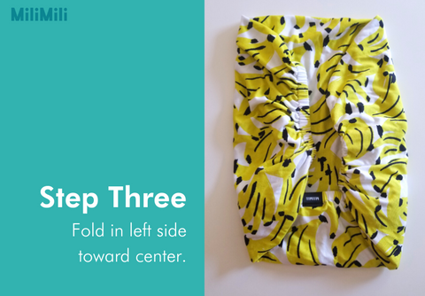 How to fold a crib sheet: step three - fold in left side towards center. Banana print cribsheet from MiliMili.