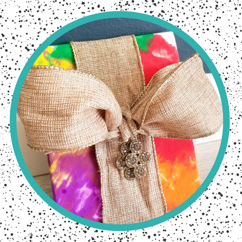 giftwrap made from child's art, tied up with burlap ribbon, and jewels hanging from tie