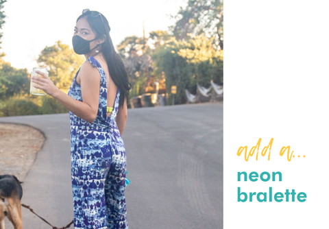 add a: neon bralette (image of woman wearing milimili playa blue romper with neon green bralette while walking dog)