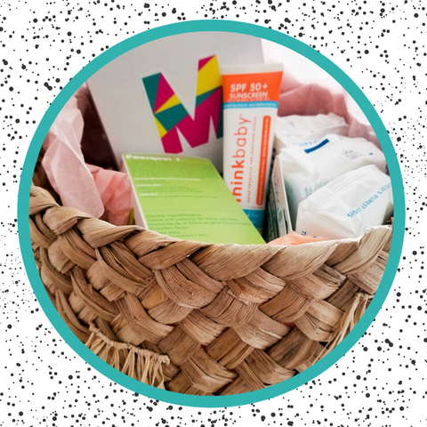 gift in a jute basket with milimili gift box, thinkbaby sunscreen, comotomo bottle, and water wipes