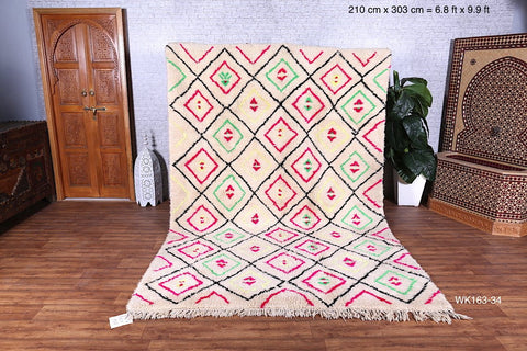white rug with neon pink and green diamond design